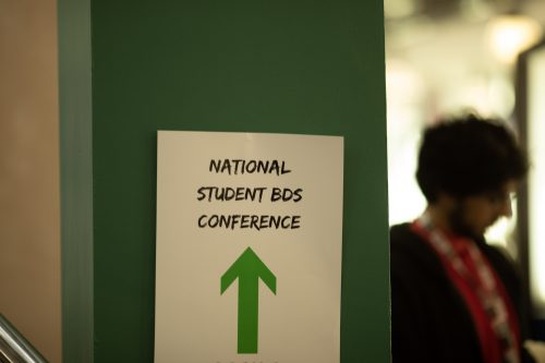 A sign/ an A4 paper with 'National Student BDS Conference typed in black caps, and a green arrow pointing up undrerneath is stuck on a green painted side of a pillar. In the background there is a blurry image of a man.