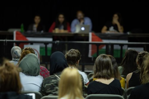 A panel consisting of three women and a man is in blurry effect, and towards the back in the image. A Palestinian flag hands on the table which they sit behind. In clear resolution, the image shows the the backs of many in the audience who are looking towards the panel.