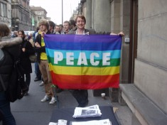 Person holding up rainbow peace flag