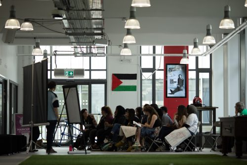 The image shows many people around a flipchart board in a workshop. The picture is taken from far, and there is a Palestinian flag hanging on a white wall behind the people in the workshop. Someone is standing near the flipchart board.