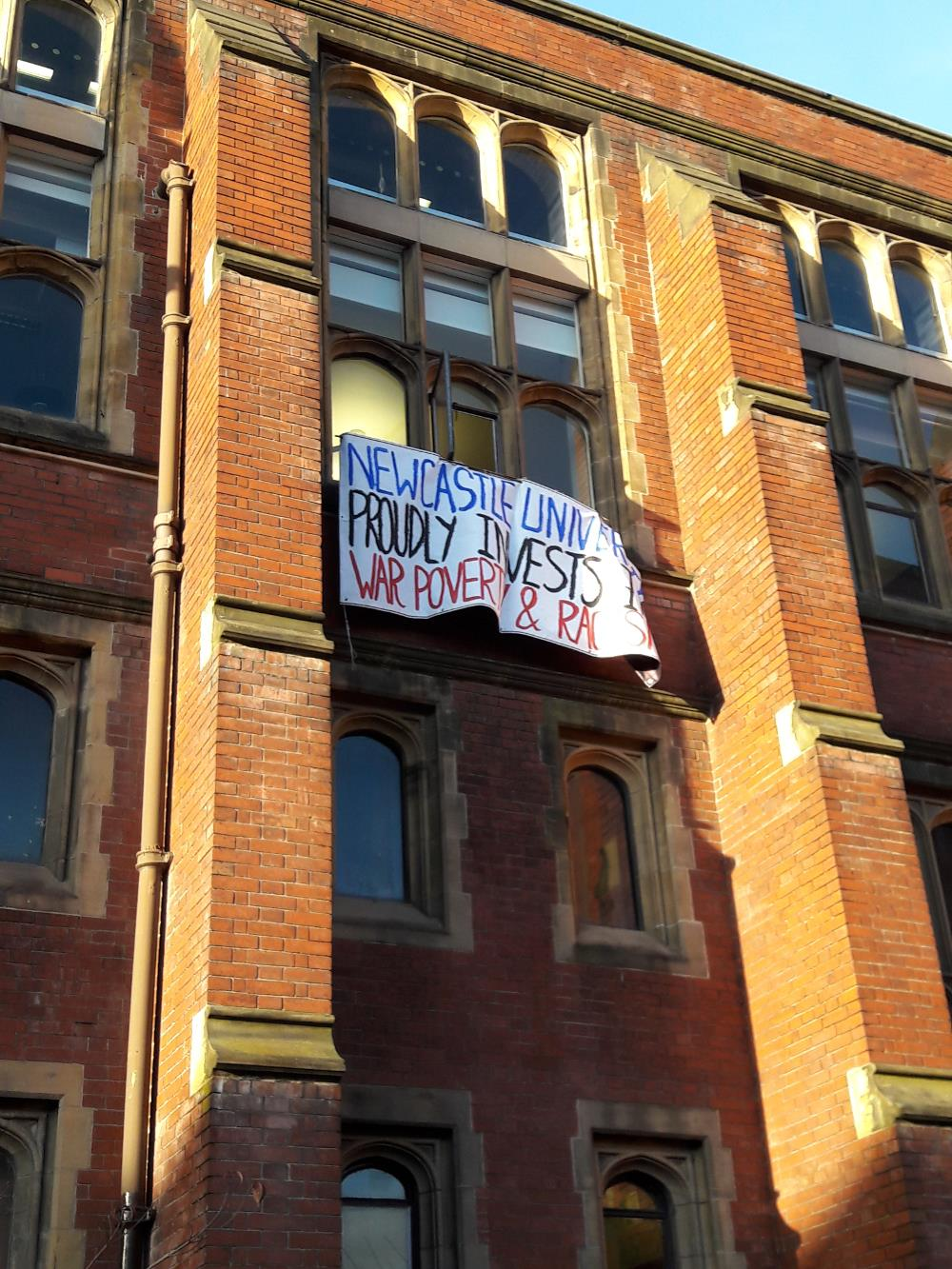 Banner unveiled on red brick building at Newcastle University