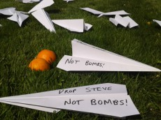 "Paper aeroplanes on grass with ""drop steve, not bombs!"" written on them"