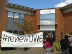 People holding a '#reviewUWE' banner outside Thales offices