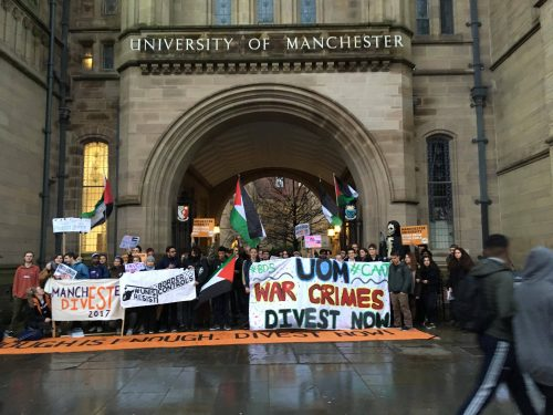 Many students stand outside the University of Manchester, holding Palestinian flags, various posters including posters stating 'Manchester University; Divest From Fossil Fuels Now'. A big banner is held at the front with 'UOM War Crimes Divest Now' and '#BDS #CAAT' written on either side. Two other banners are held at the front; one 'Unis Resist Border Controls' and one 'Manchester Divest 2017'. A long orange banner is laid on the floor in front of the students, with 'Enough is Enough. Divest Now' written in large black caps.