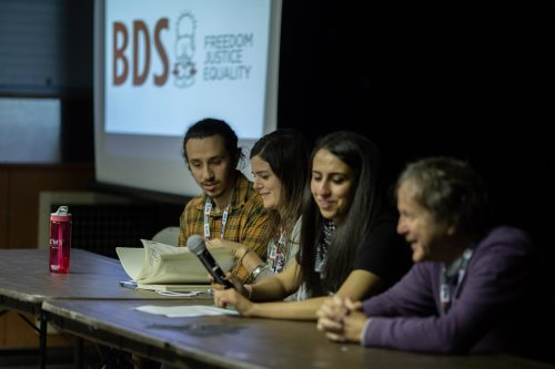 A panel consisting of two men on either side, and two women seated in the middle, all behind a wooden table. The woman in the middle right is holding a microphone. In the background, there is the projector with a slide with the BDS symbol of Handala in the middle on a white background. On the left is 'BDS' written in big red caps and on the right there is 'Freedom' 'Justice' Equality' written each on separate lines, in the respective order and in black caps.