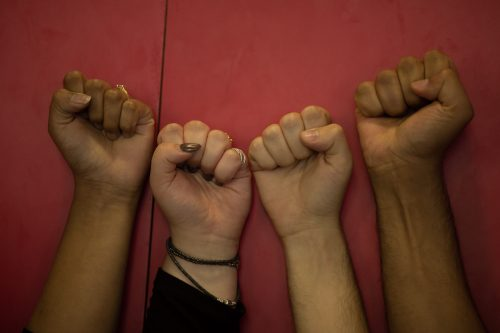4 fists are in front of a red background.