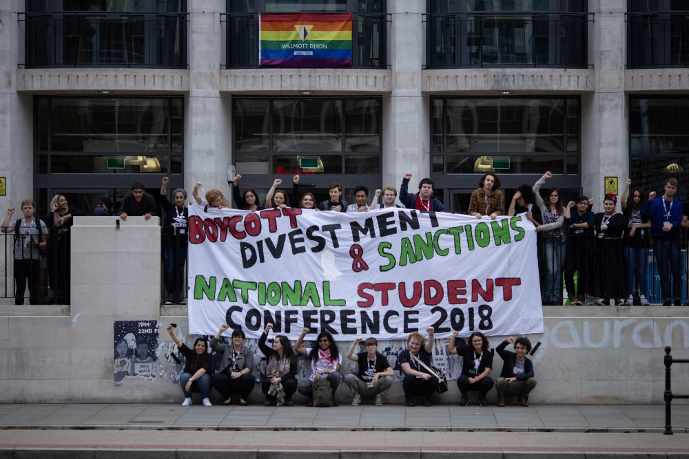 Students are gathered around a huge banner hanging from the railing outside the Manchester University Student Union. The banner reads 'Boycott Divestment & Sanctions' in diagnol alignment, and underneath ' National Student Conference 2018'. All writing is painted and in caps, and in red, black and green. Students are gathered behind the railing and on the lower level in front of it, squatted. Many have their fists in the air.