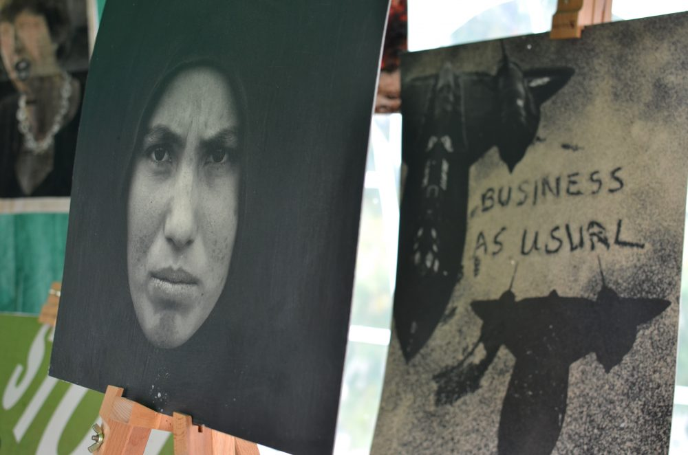 Canvases on display at Conference at the Gates; one shows a person's face in a headscarf