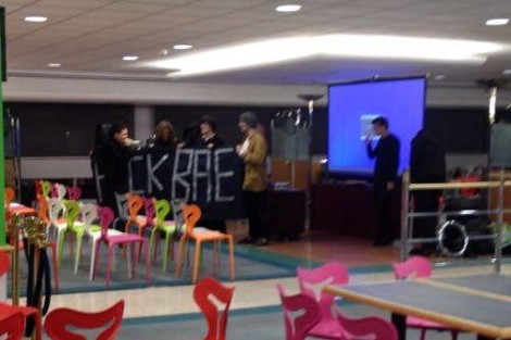 Students hold an anti-BAE banner in a room with empty chairs laid out in rows. Two people pack up presentation equipment.