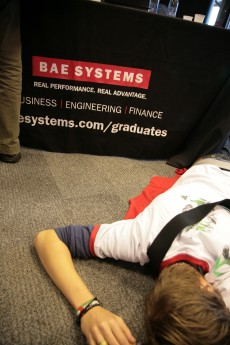 Student lying down as if dead in front of a BAE Systems stall