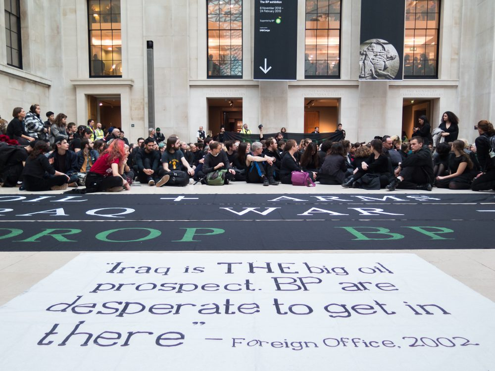 "A photo of a quote from the foreign office ""Iraq is THE big oil prospect. BP is desparate to get in there."" People are sat on the floor behind the white banner with this quote on."