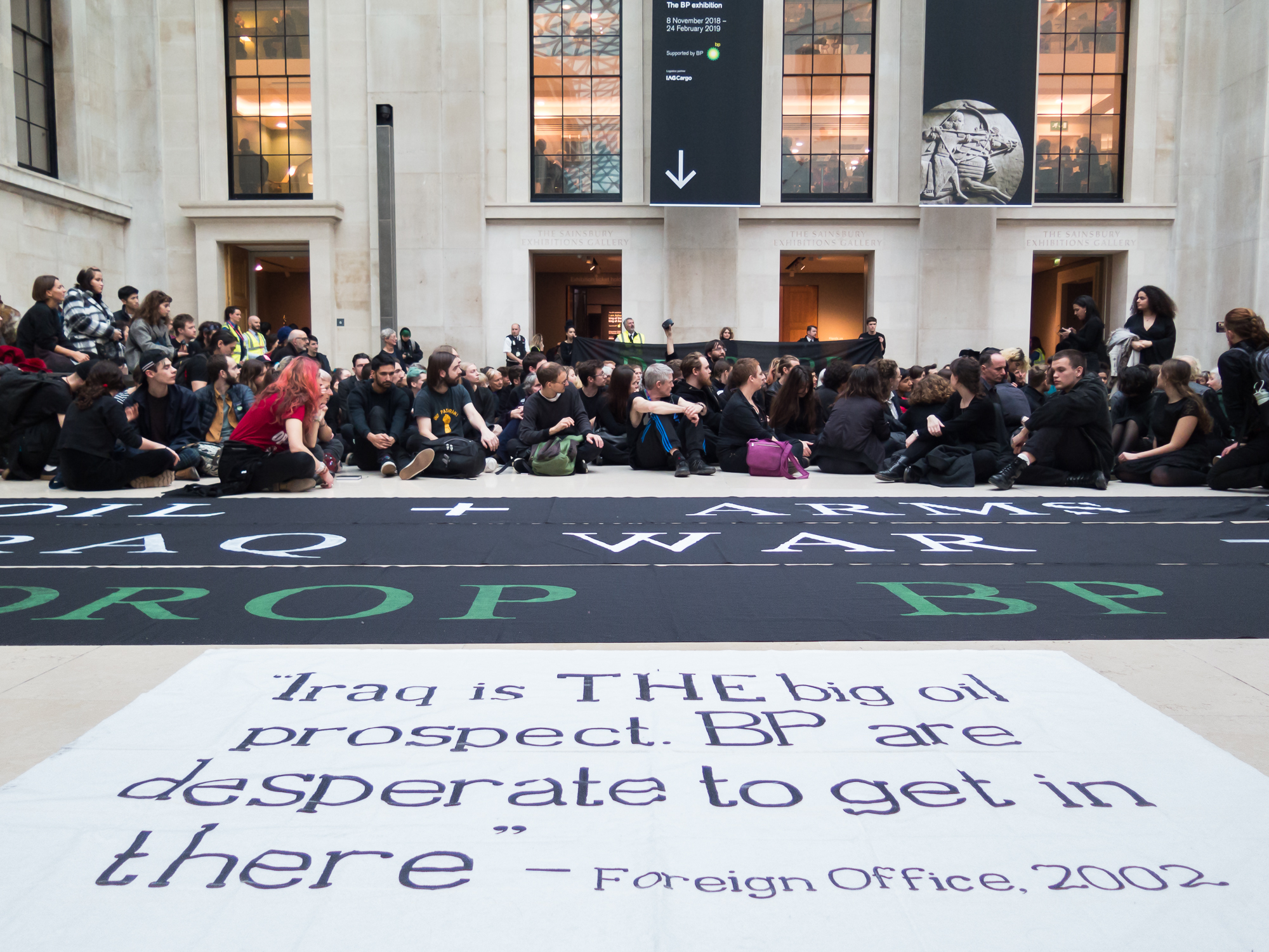 """A photo of a quote from the foreign office """"Iraq is THE big oil prospect. BP is desparate to get in there."""" People are sat on the floor behind the white banner with this quote on."""