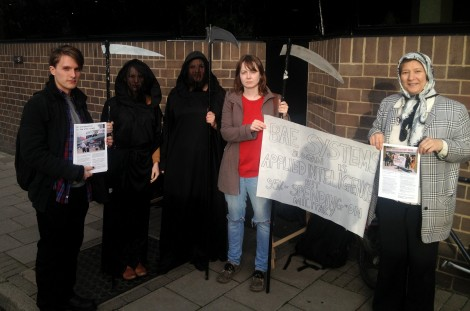 Protesters dressed as grim reapers hold a banner about BAE Systems