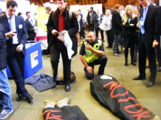 Two students lie on the floor in body bags which say 'not ok'. Security guard crouches by them.
