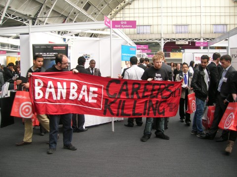 Two people standing in front of the BAE stall holding a banner that says 'Ban BAE: Careers in Killing''