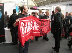 Two activists hold 'Ban BAE: Careers in Killing' banner as security guard on walkie-talkie stands in front of them