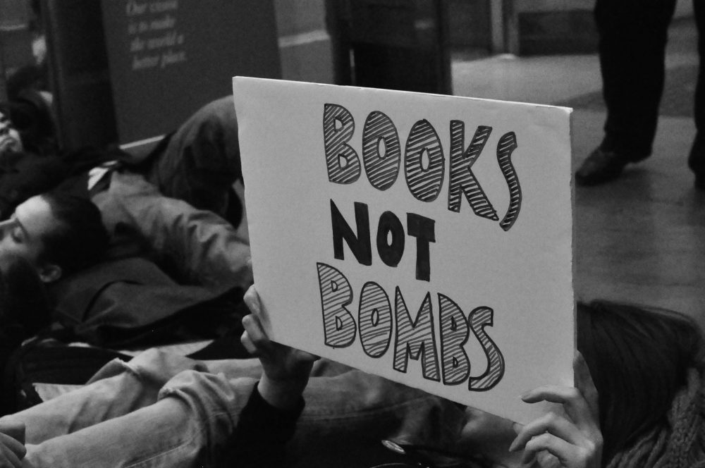 "Demilitarise King's activist in die-in holds up a sign reading ""books not bombs"""