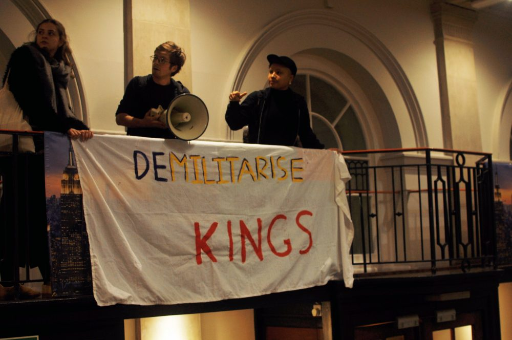 "Activists hold a banner across railings inside the Great Hall reading ""Demilitarise King's"""