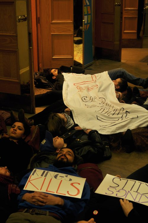 Students lay on the floor in front of doors to an event. A large banner draped over students has 'King's Kills' painted in large caps. Two other students hold small banners with the same slogan.