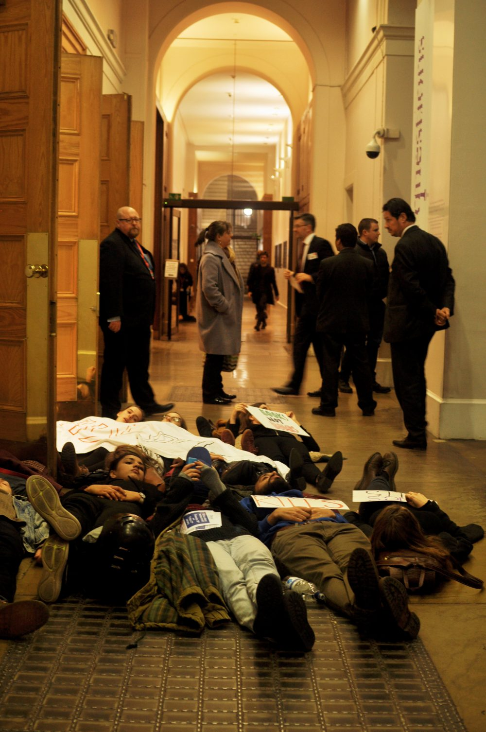 Demilitarise King's activists stage a die in in the hall way outside the Great Hall at King's College London