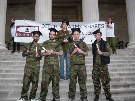 Students in camouflage and mortar boards hold graduation certificates and fake guns in front of a 'ditch the arms shares' banner