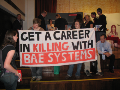 Students hold a banner which reads 'get a career in killing with BAE systems'