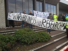 several protesters hold a banner stating that 'War is Business and Research'