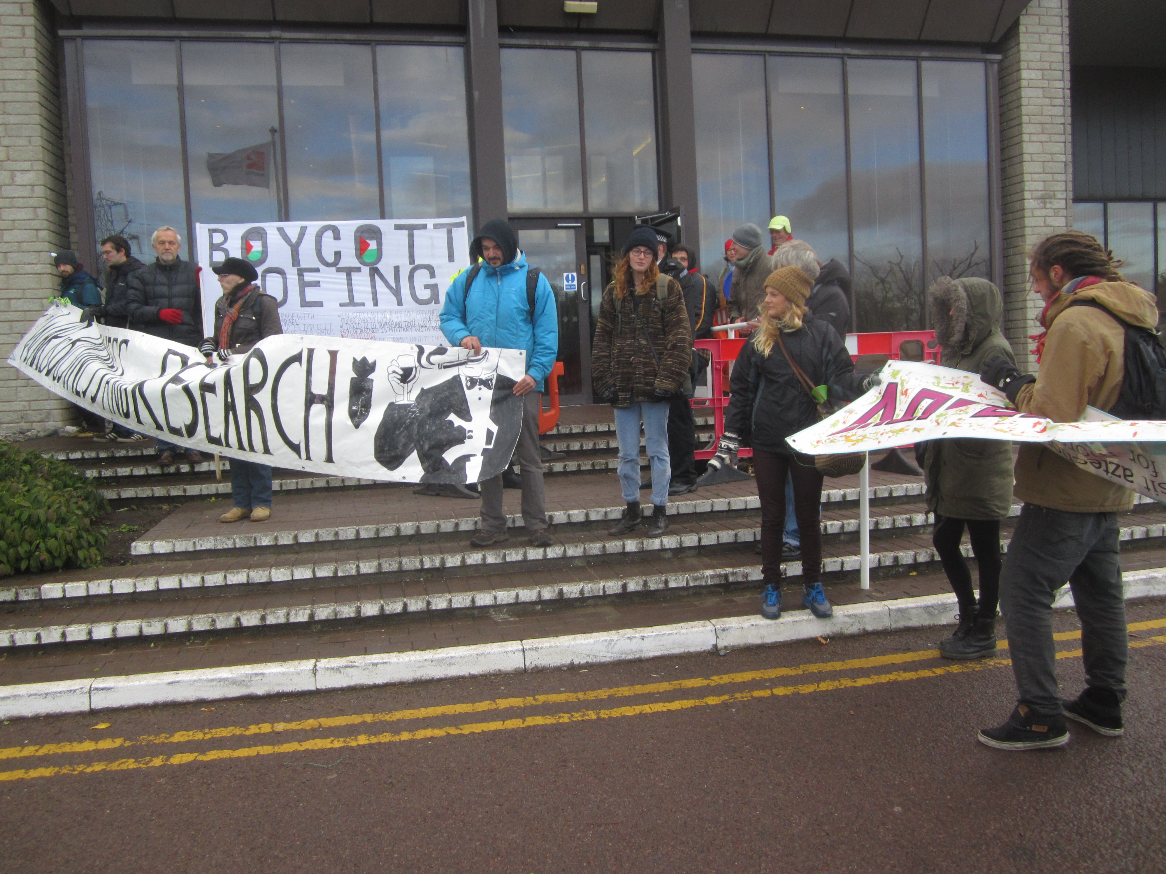 group of protesters with banners calling for boycott of the event