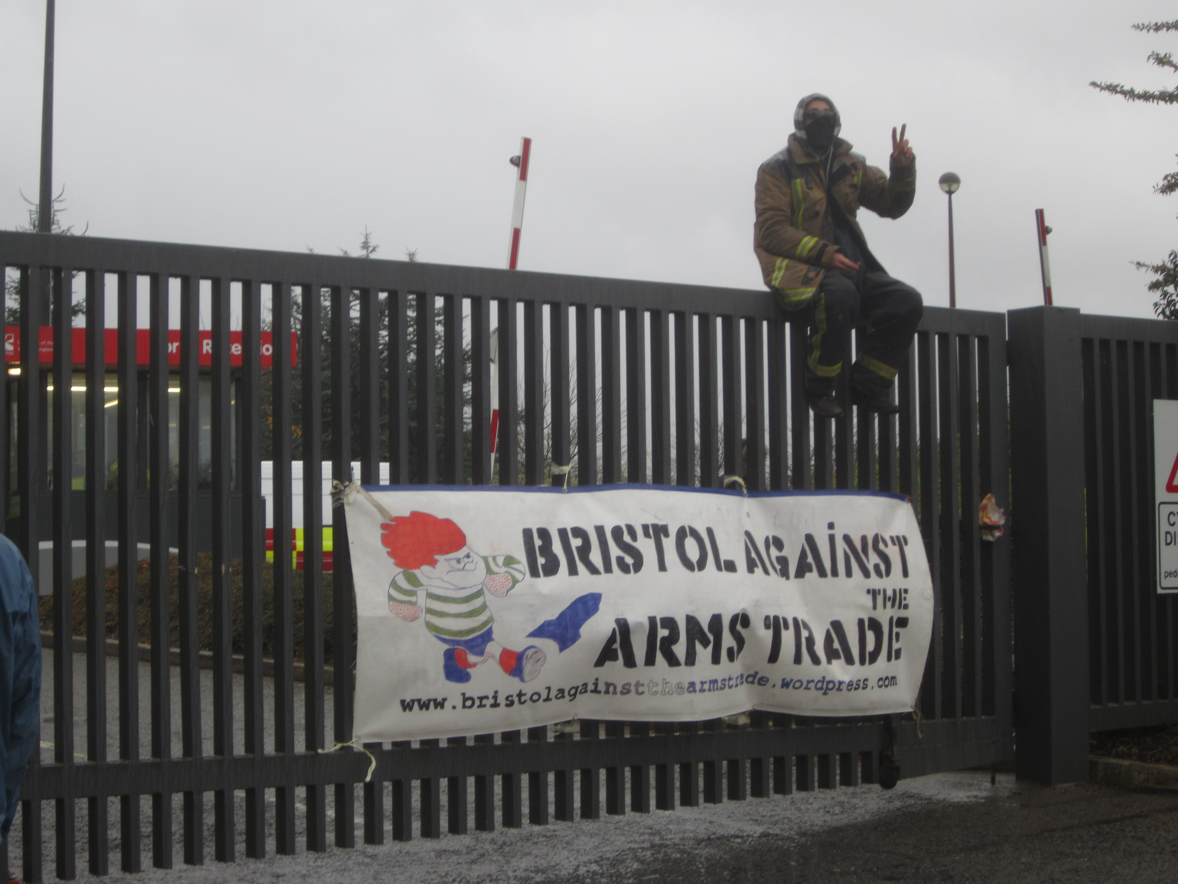 masked protester makes a peace sign with their fingers, sitting on a tall gate with a Bristol Against Arms Trade banner beneath them