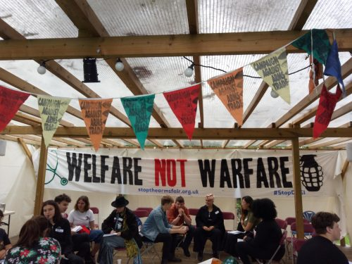 students gathered in hroups with huge 'Welfare not Warfare' banner in black caps on a white banner behind them. The 'not' is in red. Coloured bunting with a 'Campaigns Against Arms Trade' logo is hanging at the top of the image.