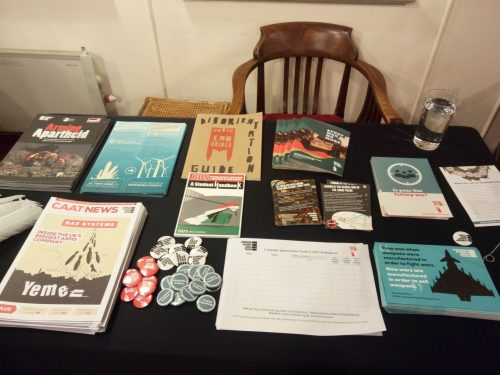 Leaflets, newsletters, mailing list, badges and flyers laid out on black tablecloth