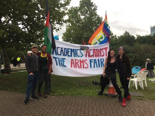 Students stand with banner which read 'Academics Against The Arms Fair'