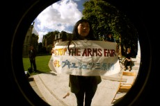 Woman holding a home-made banner reading 'Stop the arms fair' in both English and Japanese