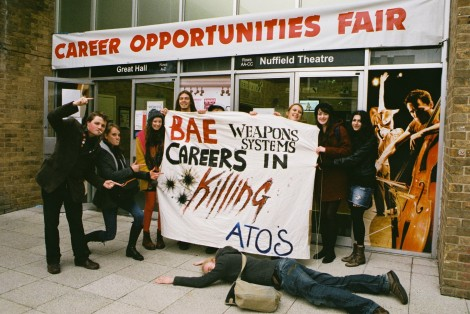 Student protesters gather with banner reading 'Careers in Killing'