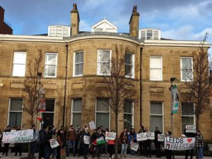 many students stand outside a building holding various banners, a Palestinian flag. Some banners state 'Apartheid Off Campus', and one big banner has a 'Leeds (love heart painted) Palestine (with a Palestinian flag painted)' painted on.