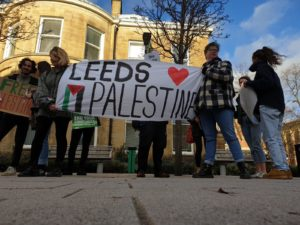 students hold a big white banner with 'Leeds' painted on in black caps with a red love heart next to it on the right hand side. Underneath 'Palestine' is painted in big black caps with the Palestinian flag painted vertically next to it, on the left hand side.