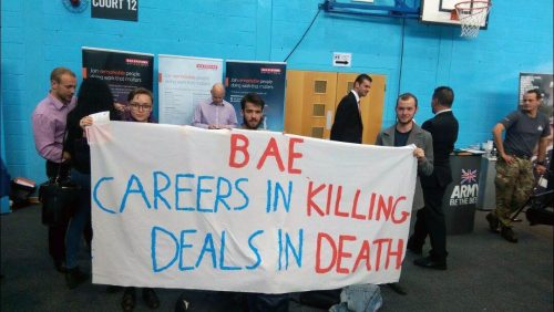 "Three students hold banner outside BAE careers fair stall reading ""BAE Careers in killing deals in death"""