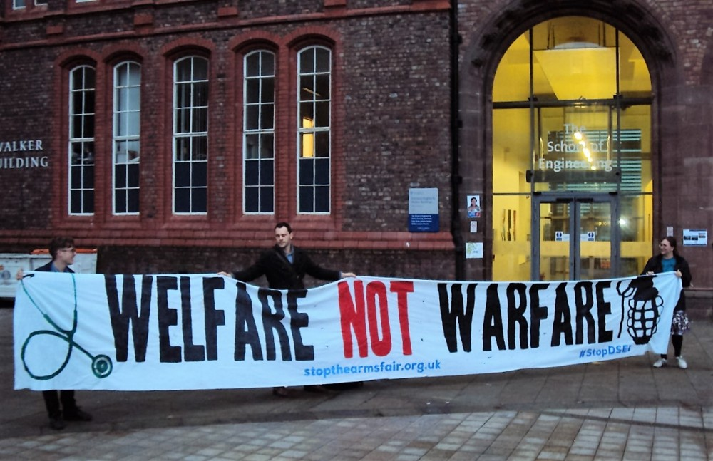 """Three students hold a banner reading """"Welfare not Warfare"""" in front of a building signed as """"The School of Engineering""""."""