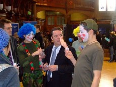 Protesters dressed as clowns talk to staff at a careers fair