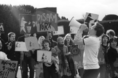 Disarm York student protest. Student in foreground with megaphone and students in background with placards