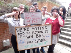 "Group of students hold their noses behind a sign saying, ""We're voting for the motion to ban BAE... they stink"""