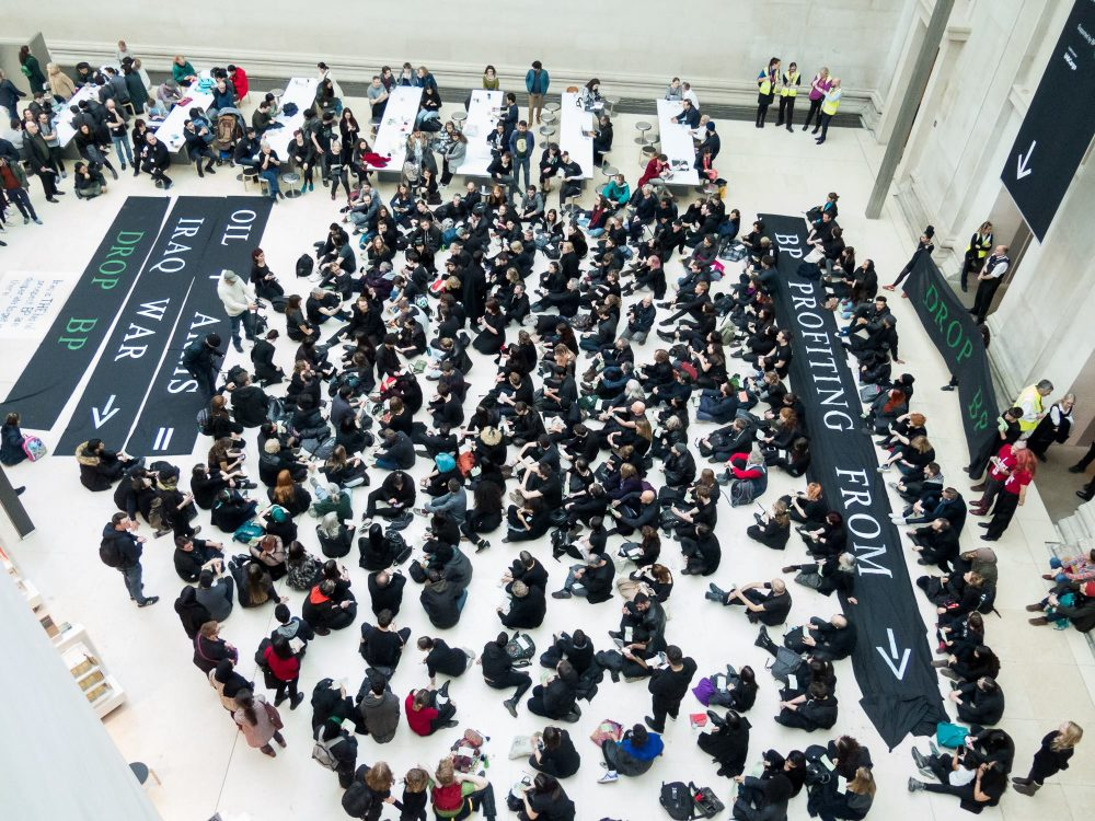Hundreds of protestors sit on the floor of the British Museum with the banners about oil, arms and the Iraq war laid down.A quote from the foreign office stating ' Iraq is the big oil prospect. BP is desparate to get in there.' is also on a banner.