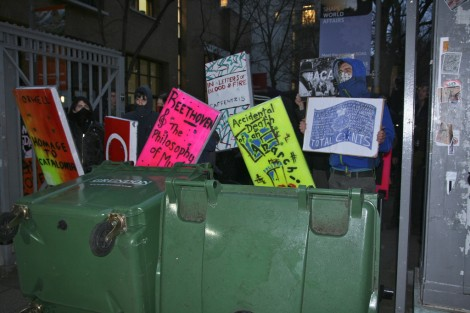Masked protesters stand behind giant cardboard books and upturned bins