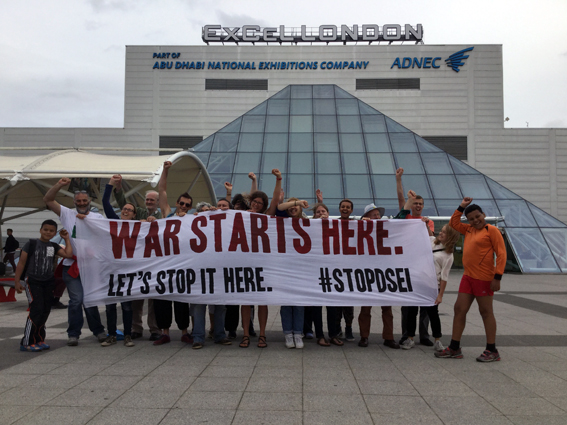 """War Starts Here - Let's Stop it Here"" banner held by activists outside the Excel Centre"