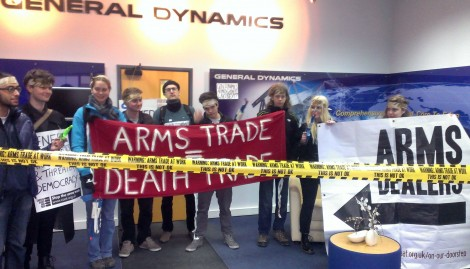 "Students stand inside General Dynamics with ""arms trade equals death trade"" banner"