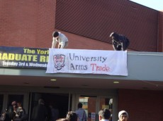 York students put a banner reading 'University Arms Trade' next to the Careers Fair banner